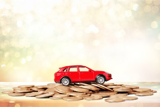 Golden coins and toy car on  background