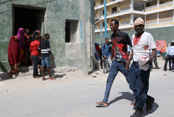 Civilian assists a man injured following an explosion near president's residence in Mogadishu