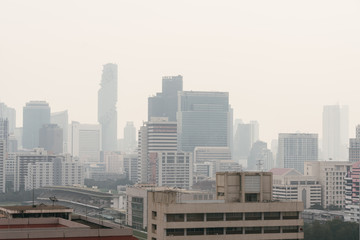 Air pollution effect made low visibility cityscape with haze and fog from dust in the air during sunset in Bangkok, Thailand. Image contain noise and grain.