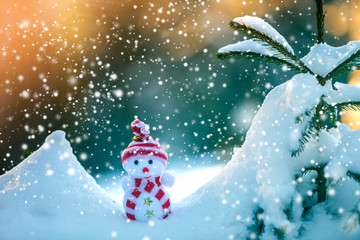 Small funny toy baby snowman in knitted hat and scarf in deep snow outdoors on bright blue and white copy space background. Happy New Year and Merry Christmas greeting card.