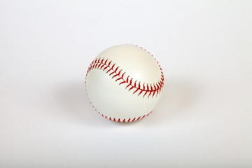 Close-up on a white baseball ball stitched with red thick thread made of genuine leather for the American team game on a white isolated background