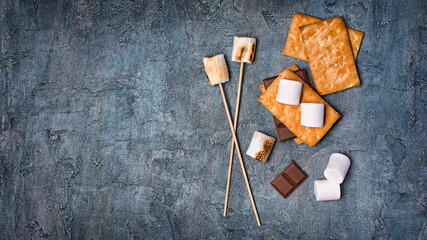 Top view on roasted marshmallow, crackers and chocolate as ingredients for s'mores