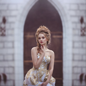 Portrait of a Beautiful woman in an ancient medieval dress, with a high complex historical hairstyle near the walls of the castle.