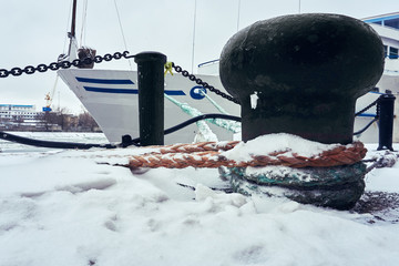 The ship is moored in the port in winter under snow with thick ropes to the bollard
