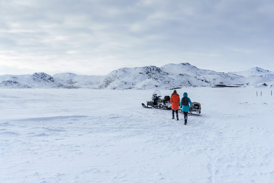 two girls in bright jackets run to their snowmobile left on the hill after a heavy snowfall on a frosty day during the expedition to the polar region