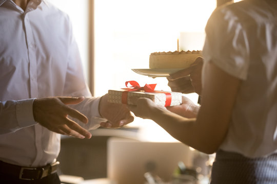Colleagues greeting congratulating coworker receiving gift box and birthday cake, friendly employees make surprise giving presents to office worker, corporate party celebration concept, close up view