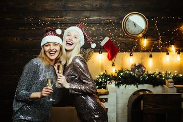 Christmas preparation. Luxury two girls celebrating New Year. Christmas girlfriends dress for girlfriends. Pretty two girls wearing in Christmas dress.