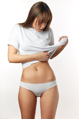 Attractive caucasian woman in white underwear demonstrates her flat belly, isolated over white background. Model of sports, dieting, fitness or plastic surgery and aesthetic cosmetology