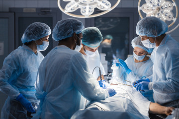 Group of concentrated surgeons engaging in rescue of male patient in operation room at hospital, emergency case, surgery, medical technology, health care and disease treatment concept