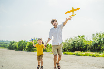 Happy father and son playing with toy airplane against old runway background. Traveling with kids concept
