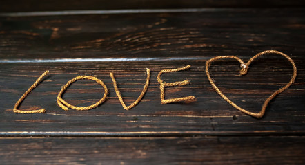 inscription love from a beautiful rope with a heart on a wooden background, valentines day