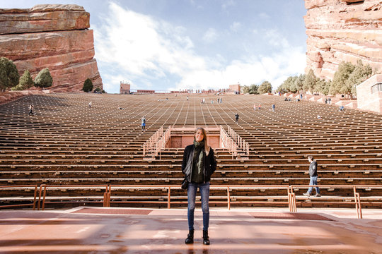 Portrait of Female Person Standing Front and Center on a Stage Dreaming and Imagining the Future while Facing Stadium Stands at Outdoor Amphitheater Concert Music Hall