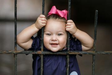 Preschool Toddler Little Girl Looking through Iron Gate Fence