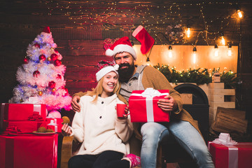 Merry Christmas and Happy New Year. Cute young woman and handsome man with Santa dress. Positive human emotions facial expressions.