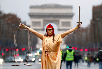 "A woman dressed as Justice and French republic symbol ""Marianne"" poses during a demonstration by the ""yellow vests"" movement on the Champs Elysees near the Arc de Triomphe in Paris"