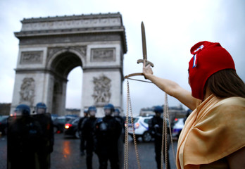 "A woman dressed as Justice and French republic symbol ""Marianne"" poses during a demonstration by the ""yellow vests"" movement near the Arc de Triomphe in Paris"