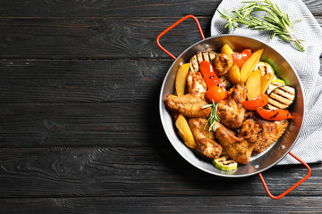 Wok with barbecued chicken wings and garnish on wooden background, top view. Space for text