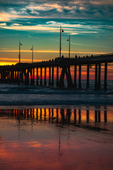 Rainbow sunset with pier and strong reflection