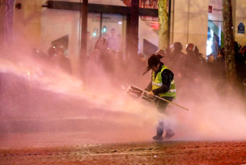 """A protester wearing a yellow vest is sprayed with water by a water cannon during a demonstration by the """"yellow vests"""" movement on the Champs Elysees near the Arc de Triomphe in Paris"""