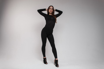 Young attractive woman with brown long hair with a beautiful figure in a black fashionable t-shirt in stylish leggings and leather shoes with heels is dancing in a studio near a white wall. Nice girl