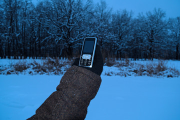 View of the hand with a mobile phone on the background of a snowy lake near the winter.