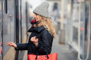 Woman Hold Her Red Bag While Opening Door To Tram. Portrait Of Stylish Smiling Woman In Winter Clothes Holding Bag. Female Winter Style. - Image