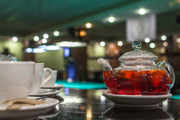 Glass teapot. Fruit and citrus tea. Hot morning drink. A warming drink with pieces of fruit. Glass teapot for tea. Beautiful tea service in the restaurant.