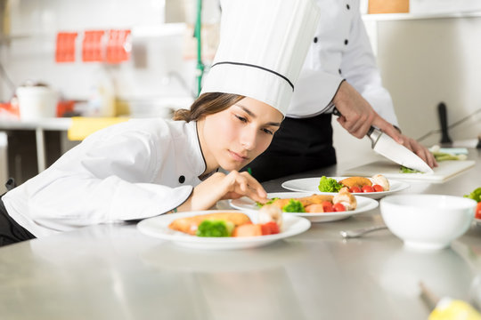 Chef Arranging Basil Leaves In Plate