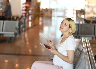 Pregnant woman is traveling by plane sitting at seat.