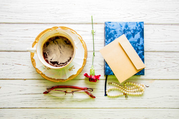Cup of coffee on a saucer, red carnation, glasses, diary, envelope and pearl beads on a light wooden background. view from above