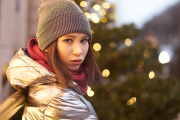 portrait of a beautiful girl. girl in a winter shiny jacket a red scarf and hat. on the background of Christmas lights. bokeh Garlands. decorated christmas tree