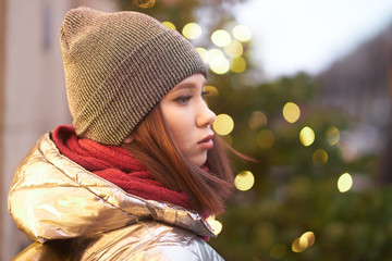 portrait of a beautiful girl looking into the distance the girl at the decorated shop window. girl in a winter shiny jacket a red scarf and hat. on the background of Christmas lights. bokeh Garlands