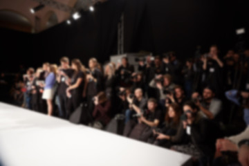 blurred image of group of audience at fashion show stage.
