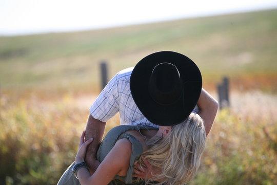 Cowboy kissing woman in field