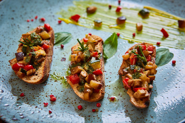 Vegan food: bruschetta with bell pepper, tomatoes, arugula, thyme and basil