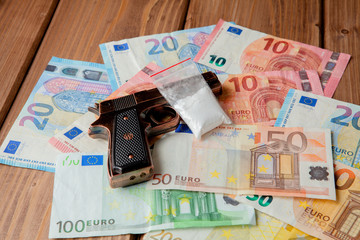 Black gun and packets of drugs against the background of the euro on a wooden table