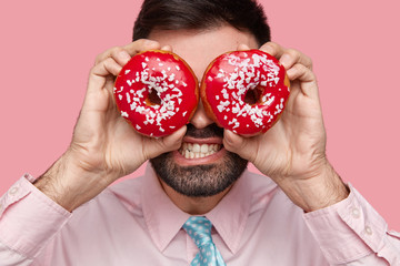 Close up shot of bearded businessman in light pink formal shirt covers eyes with two delicious doughnuts, clenches teeth, feels temptation, being hungry, isolated over studio wall. Sweet dessert