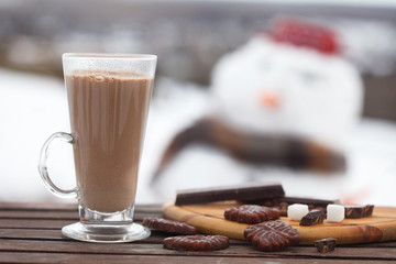 Glass of hot chocolate or cocoa with cookies and chunks of dark chocolate on  wooden table. Snow white in blurred background.