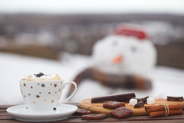 Cup of hot coffe or espresso with cream, cookies and chocolate on wooden table. Snow white in blurred background.