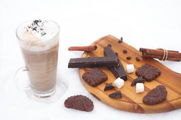 Glass of hot chocolate, cinnamon sticks, cookies and chocolate on snow. Winter refreshment.
