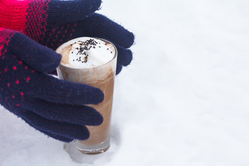 Glass of hot chocolate with whipped cream on snow. Two hands in gloves taking glass with warm drink.