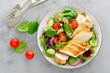 Stores à enrouleur Nourriture Grilled chicken breast, fillet and fresh vegetable salad of lettuce, arugula, spinach, cucumber and tomato. Healthy lunch menu. Diet food. Top view