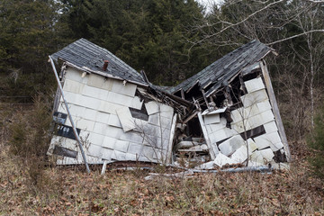 Relic farm house collapsing in on itself with large trees