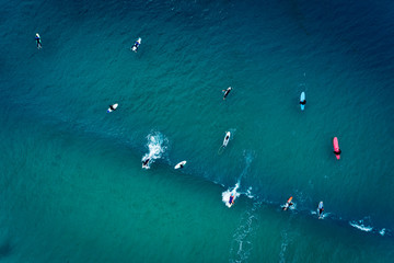 Aerial view of a group of surfers in the ocean at the Baleal beach in Peniche, Portugal