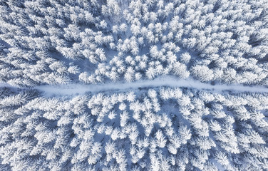 Photo sur Plexiglas Vue aerienne Aerial view on the road and forest at the winter time. Natural winter landscape from air. Forest under snow a the winter time. Landscape from drone