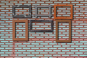 Old photo frames on bricks wall. Wooden picture frame.