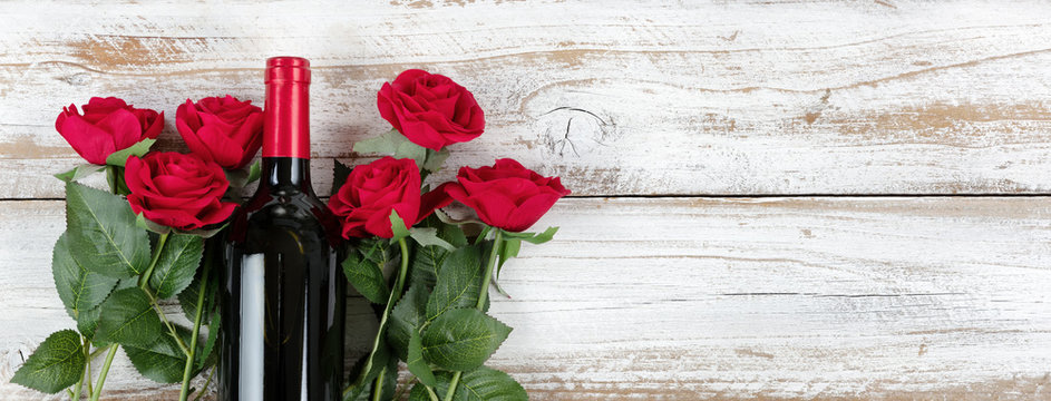 Valentines Day celebration with red wine and roses on white rustic wood