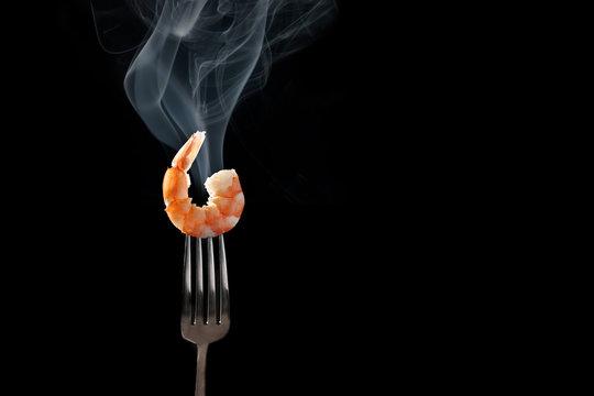 shrimp on fork isolated black background