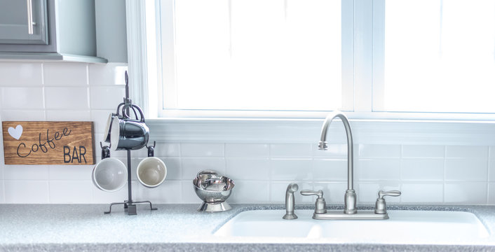 Kitchen sink with coffee mugs by bright window