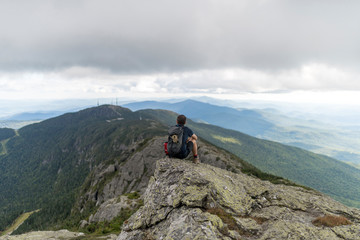 a hiker enjoys the unparalled views atop a high mountain range in Vermont